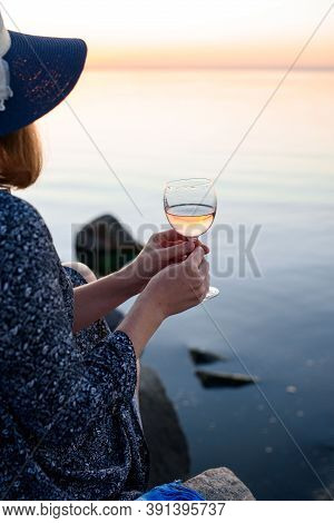 A Beautiful Glass With Pink Wine In The Hands Of A Young Girl. A Glass Of Wine At Sunrise. Romantic