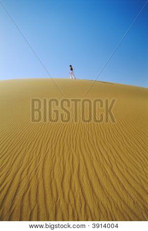 Woman Walking Across Desert
