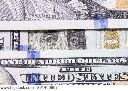 Benjamin Franklin's Eyes Between Hundred Dollar Banknotes Close-up. 100 Dollar Bill With Only Eyes O