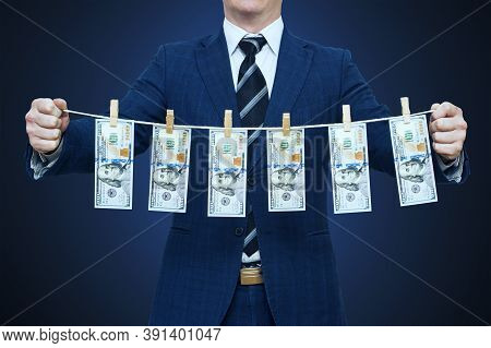 Businessman Shows Laundered Money. Businessman Holding Money Hanging On A Rope