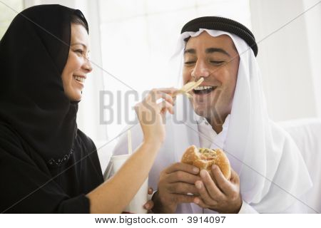 Middle Eastern Couple At Home Eating Fast Food