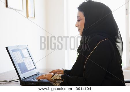 Middle Eastern Woman Sat In Home Office Using Laptop