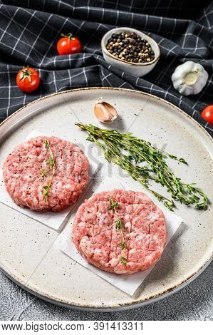 Raw Pork Patty, Ground Meat Cutlets On A Cutting Board. Organic Mince. Gray Background. Top View