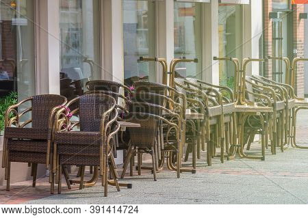 Stacked chairs and tables in front of a closed restaurant in the city center. Restrictions related to the Coronavirus Covid-19.