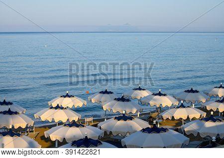 Colorful Parasols On Sandy Beach Of Medieval Small Touristic Coastal Town Sperlonga, Latina, Italy O