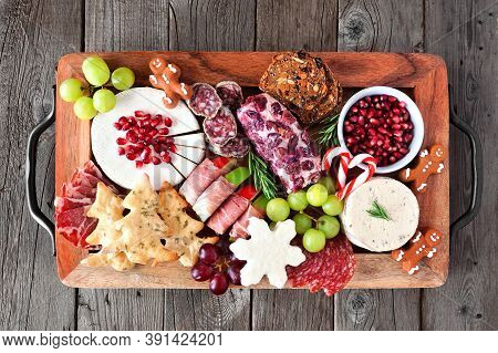 Christmas Theme Charcuterie Board. Above View Against A Dark Wood Background. Variety Of Cheese And