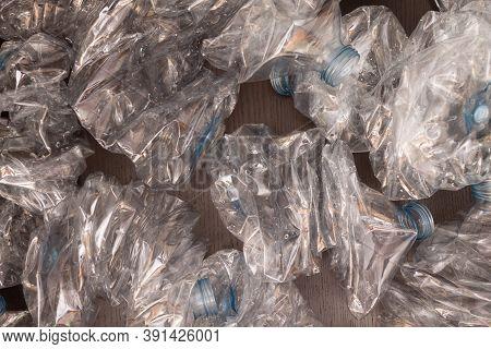 Plastic Bottles Background. Empty Bottles On Black Surface. Non Biodegradable Waste