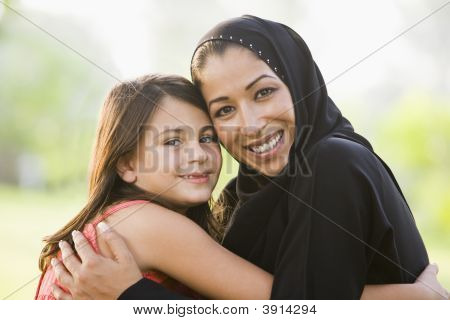 Middle Eastern Woman Sat In Park With Daughter