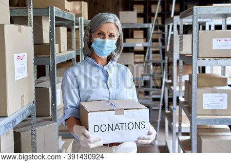 Mature Female Warehouse Worker Volunteer Wearing Face Mask Standing In Shipping Storage Delivery Cha