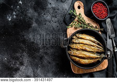 Fried Smelt In The Pan On The Table With Tomatoes And Pepper. Black Background. Top View. Copy Space