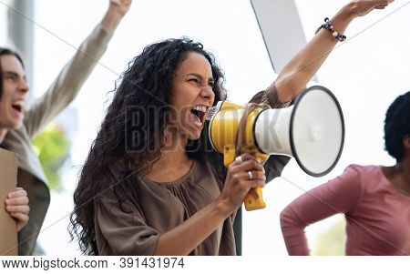 Closeup Of Motivated Young Woman With Loudspeaker Leading International Group Of Strikers, Demonstra