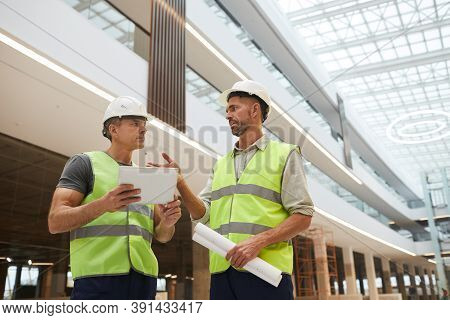 Low Angle Portrait Of Two Professional Building Contractors Using Digital Tablet While Standing At C