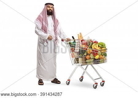 Arab man standing with a shopping cart full of food products isolated on white background
