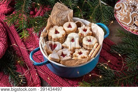 Linzer Christmas Cookies Filled With Marmalade, With Fir Branches And Gingerbread Cookies In The Bac
