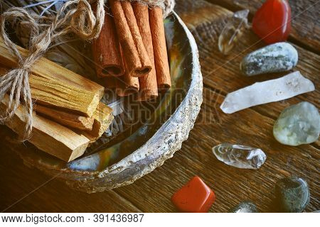 A Close Up Image Of Smudge Kit With A White Sage Bundle, Cinnamon Sticks, And Palo Santo In A Abalon