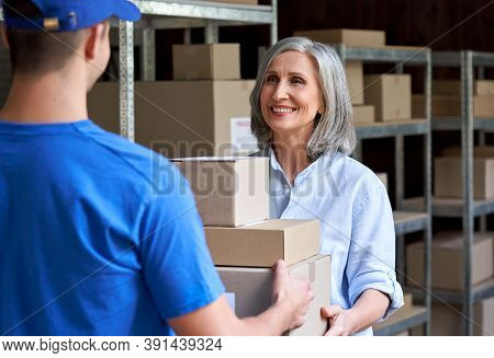 Happy Mature Female Manager Small Business Owner, Seller, Supervisor Giving Fast Drop Shipping Safe