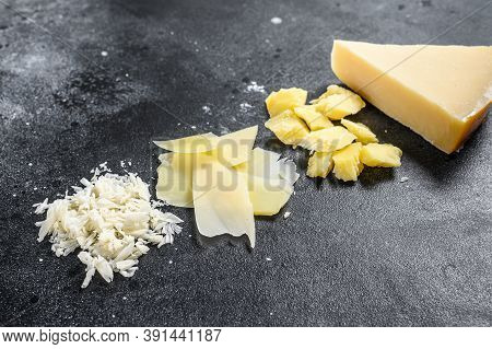 Italian Hard Parmesan Cheese Slice, Cut, Grated. Black Background. Top View