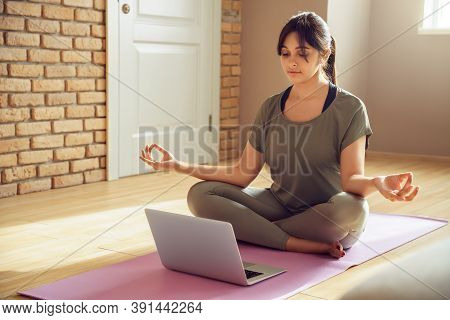 Young Healthy Indian Woman Wear Sportswear Meditating Watching Live Online Tv Pilates Class Tutorial