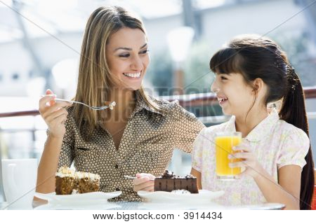 Middle Eastern Woman And Child Eating And Drinking In Shopping Mall