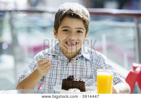 Middle Eastern Child Eating And Drinking In Shopping Mall