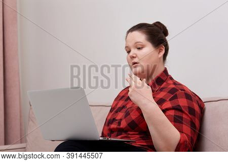 Beautiful Woman Plus Size Model Working Online With Laptop On Her Lap.