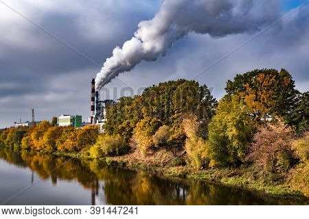 Pipes Of Woodworking Enterprise Plant Sawmill Near River With Autumn Red Yellow Trees. Air Pollution