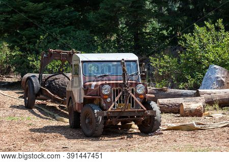 Prospect, Oregon / Usa - August 16, 2014:  An Antique Jeep With A Trailer Hauling A Large Log At The