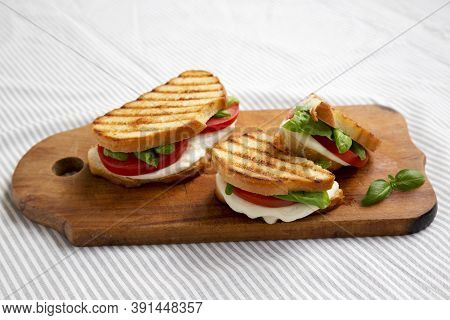 Tasty Grilled Caprese Panini (mozzarella, Tomatoes And Basil) On A Rustic Wooden Board, Side View.