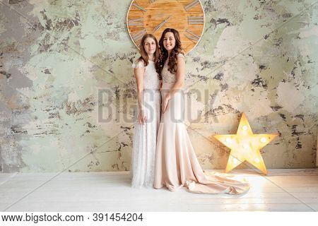 Two Gorgeous Young Women Dressed In Exquisite Nude Long Dresses With Lace Top. Attractive Female Mod