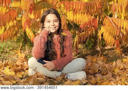 Knowledge For Early Age. Cute Small Girl With Book Sit On Autumn Leaves. Adorable Little Child Get K