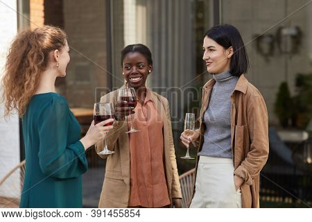 Multi-ethnic Group Of Contemporary Adult Women Chatting While Enjoying Wine At Outdoor Party, Copy S