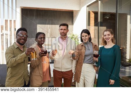 Waist Up Portrait Of Multi-ethnic Group Of Friends Looking At Camera While Enjoying Wine Standing At