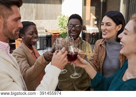 Portrait Of Multi-ethnic Group Of Friends Clinking Glasses While Enjoying Wine During Outdoor Party