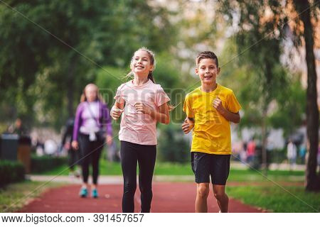 Sports And Fitness In Adolescence. Caucasian Twins Boy And Girl Run On The Jogging Track In The City