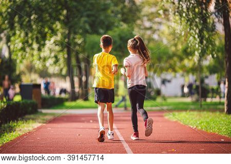 Couple Of Kids Boy And Girl Doing Cardio Workout, Jogging In Park On Jogging Track Red. Cute Twins R
