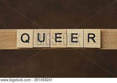 Gray Word Queer Made Of Wooden Square Letters On Brown Background