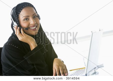 Middle Eastern Woman Using Laptop With Headset