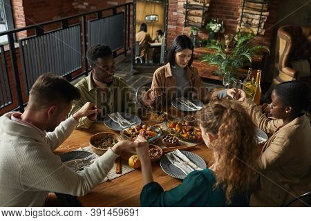 High Angle Portrait Of Multi-ethnic Group Of Elegant Young People Praying And Holding Hands While Si