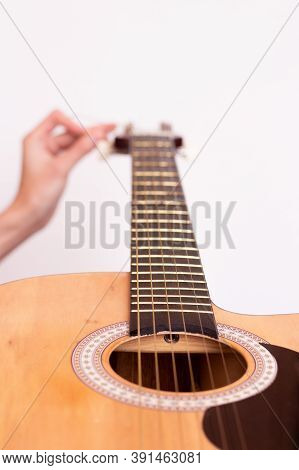 The Guy Is Tuning The Guitar. Close Plan. Wooden Guitar.