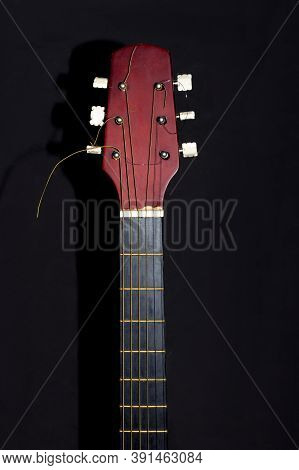 Guitar Head And Neck On A Black Background. Wooden Acoustic Six-string Guitar.