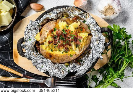 Tasty Baked Potato Topped With Cheddar Cheese And Chives. White Background. Top View
