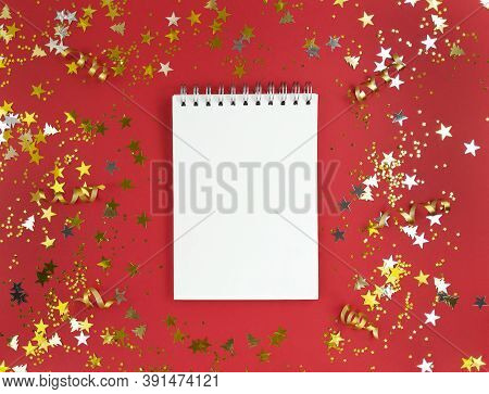 White Blank Sheet Of Notebook On A Red Background With Scattered Confetti. Holiday Education Concept