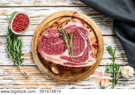 Raw Cowboy Steak Or Ribeye On The Bone On A Cutting Board. Marble Beef. White Wooden Background. Top