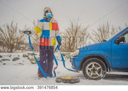 Man With Towing Rope Hooks Near Towed Car. Wear Medical Masks Due To The Covid-19 Coronavirus