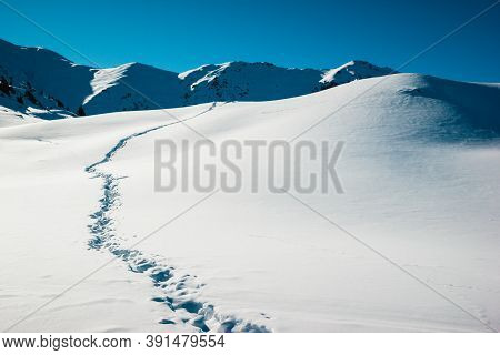 Path Trail On Winter Sunrise, White Snow Field On The Background Of Frozen Mountains