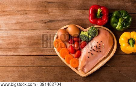 Top View Of Raw Chicken Breasts Fillets No Boneless With Spices Rosemary, Carrot, And Eggs In Heart