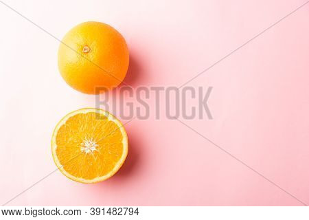 Top View Of Fresh Half Orange Fruit Slice And Full Orange In The Studio Shot Isolated On Pink Backgr