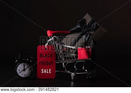 Black Friday Sale Concept, Gift Box Wrapped In Black Paper And Black Bow Ribbon In The Shopping Cart