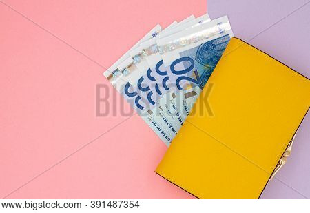 Close-up Of Yellow Wallet With 20 Euro Banknotes On A Colored Background