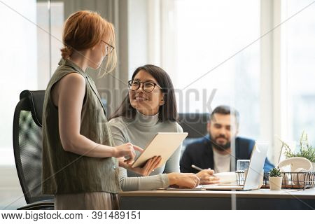 Young Asian businesswoman and her Caucasian colleague looking at one another while consulting about points of presentation for conference